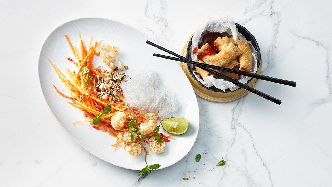 Salade de nouilles chinoises transparentes et carottes, servie avec des rouleaux de printemps croustillants