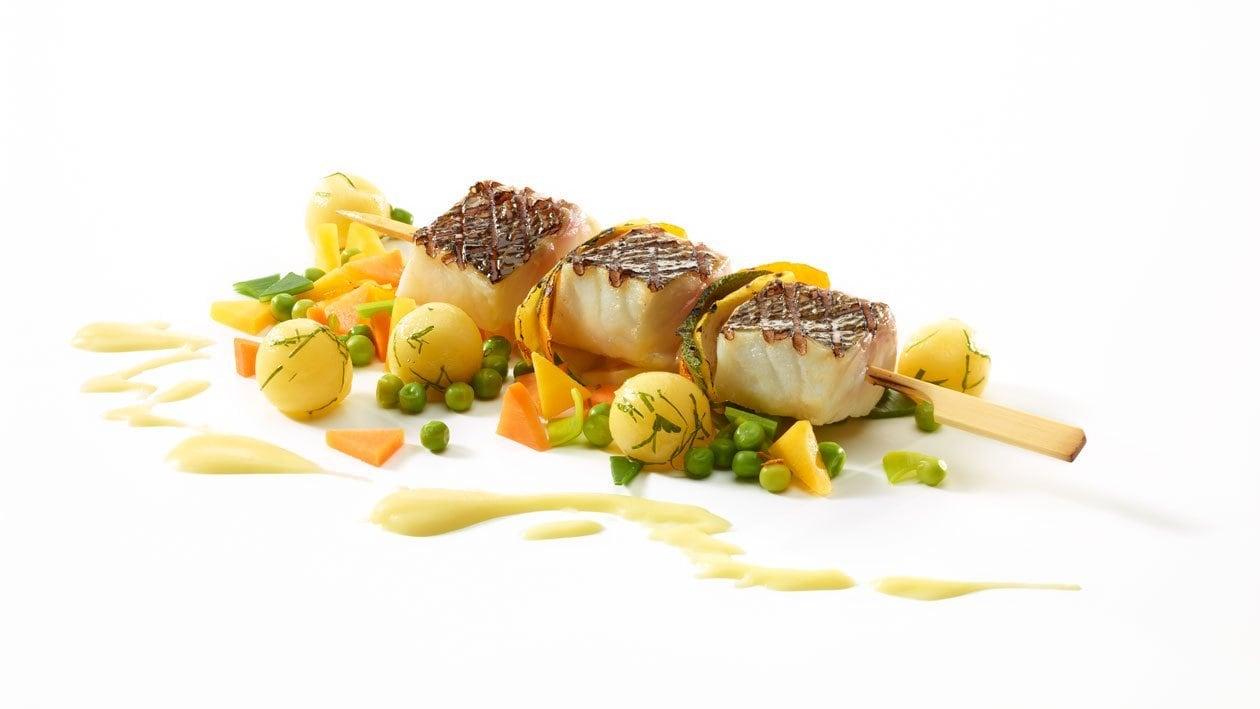 Brochette de loup de mer sur pommes de terre aux légumes et sauce Parmentier
