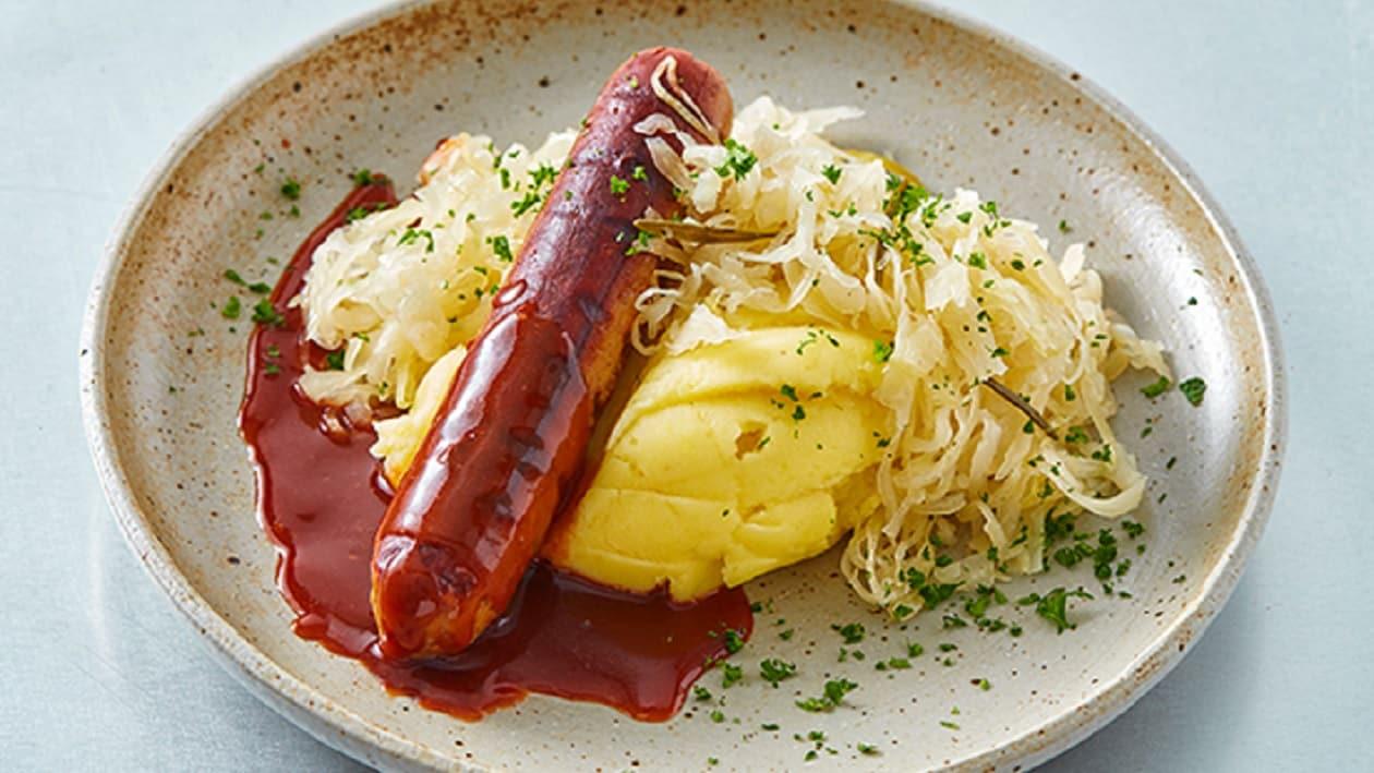 Saucisse végétarienne rôtie servie avec un jus, une pomme purée et de la choucroute